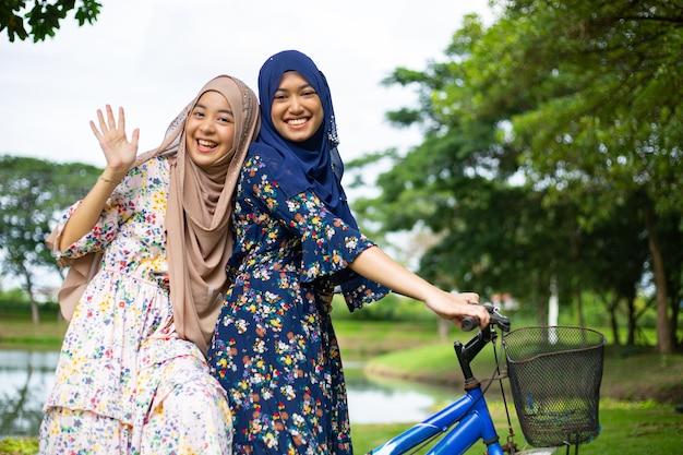 Duas mulheres muçulmanas andam de bicicleta para viajar no jardim.