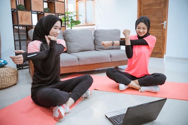 Duas mulheres muçulmanas em roupas esportivas se aquecem com uma mão segurando a outra quando uma delas é puxada para o lado enquanto realizam atividades conjuntas em casa