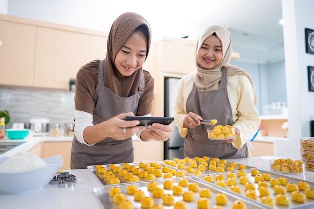 Duas mulheres muçulmanas tirando foto de um produto alimentício que fizeram em casa, uma pequena empresa vendendo muçulmanos