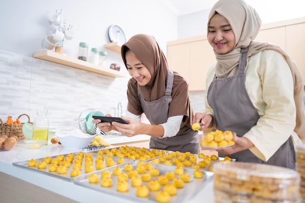 Duas mulheres muçulmanas tirando foto do produto alimentício que fizeram em casa. pequena empresa muçulmana vendendo bolo nastar