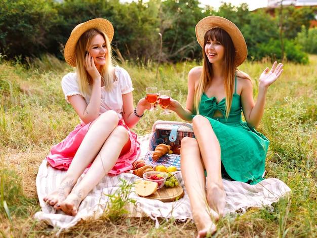 Duas mulheres muito alegres, melhores amigas, usando vestidos elegantes românticos e chapéus de palha combinando