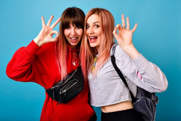 Duas mulheres muito jovens hippie mostrando um gesto ok, retrato do estilo de vida, sorrindo e olhando, feliz casal de amigos, roupas esportivas brilhantes casuais.