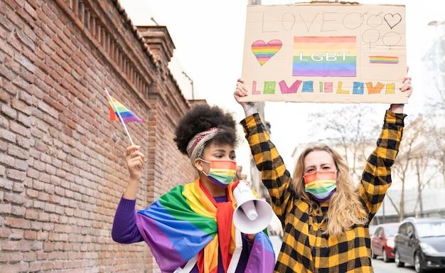 Duas mulheres multiétnicas celebrando o orgulho gay vestindo a bandeira do arco-íris, símbolo do movimento social lgbt