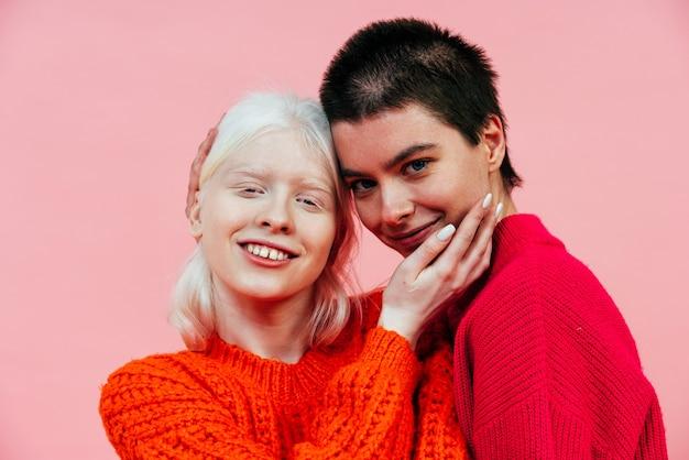 Duas mulheres multiétnicas com diferentes tipos de pele posando juntas no estúdio