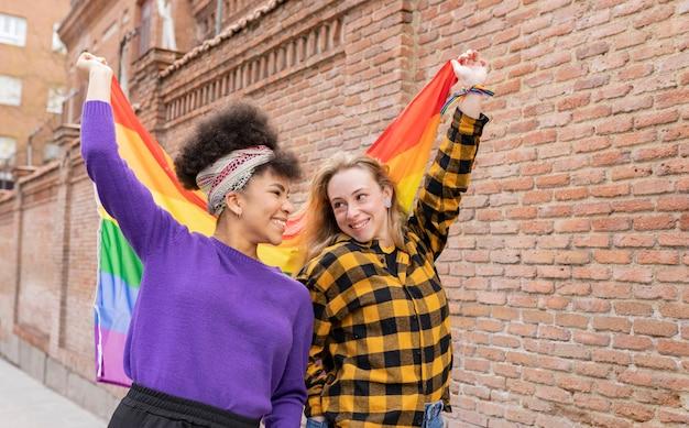 Duas mulheres multirraciais com bandeira do orgulho gay na rua