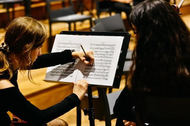 Duas mulheres músicos corrigindo uma partitura com um lápis antes da orquestra começar a tocar.
