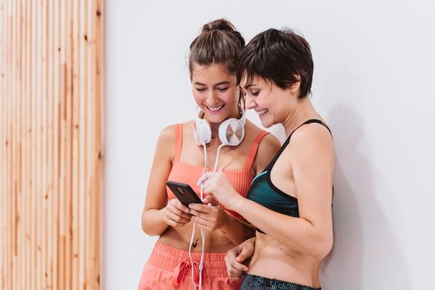 Duas mulheres na academia conversando alegremente, ouvindo música no celular
