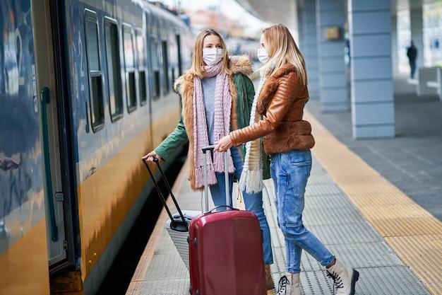 Duas mulheres na estação de trem usando máscaras devido às restrições covid-19