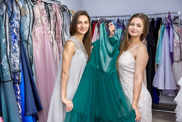 Duas mulheres na loja de roupas exibindo vestido