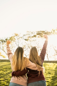 Duas mulheres na luz solar abraçam por trás