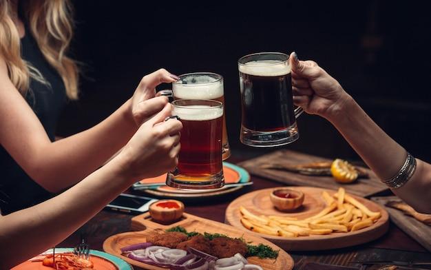 Duas mulheres na mesa de jantar com copos de cerveja.