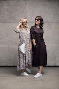 Duas mulheres na moda alegres usando óculos de sol