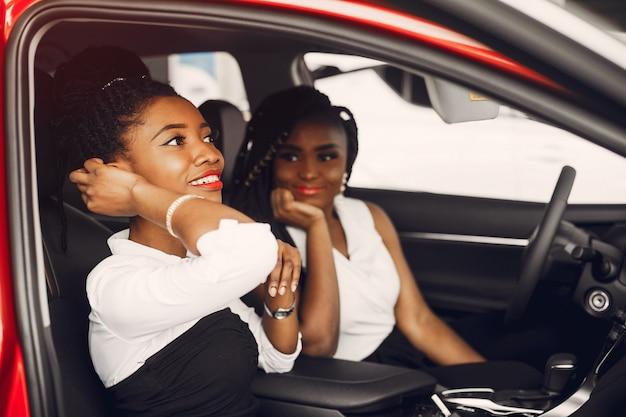 Duas mulheres negras elegantes em um salão de carro