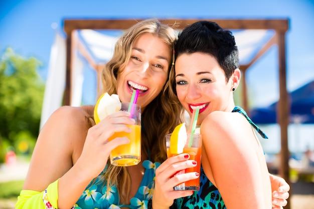 Duas mulheres no bar da praia tomando coquetéis