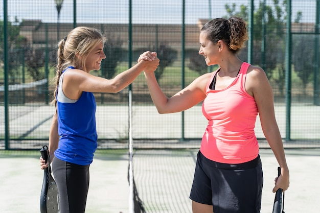 Duas mulheres no sportswear de mãos dadas com uma expressão satisfeita em uma quadra de tênis