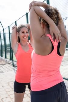 Duas mulheres no sportswear, esticando os braços na frente um do outro enquanto sorrindo