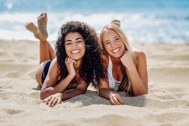 Duas mulheres novas com corpos bonitos no roupa de banho em uma praia tropical.