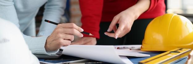 Duas mulheres olhando documentos e mostrando-os a lápis na coordenação do estúdio de design