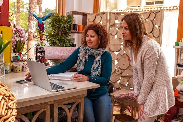 Duas mulheres olhando para o computador em uma floricultura, com enfeites