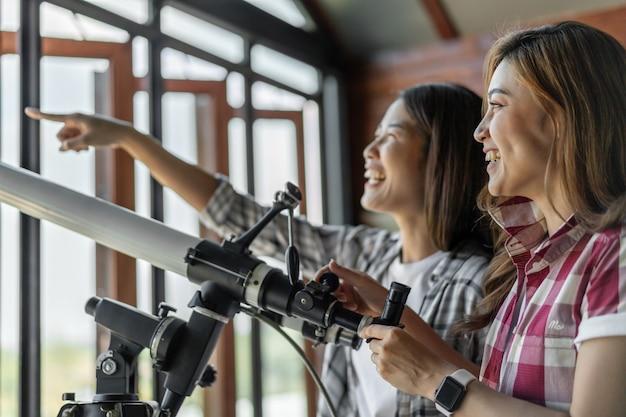 Duas mulheres, olhando, telescópio