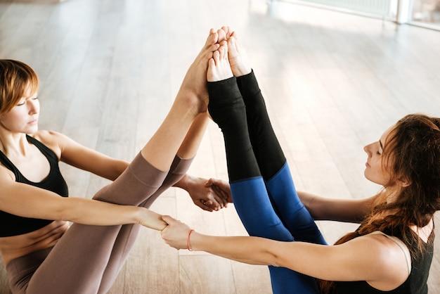 Duas mulheres pacíficas meditando e fazendo acro yoga no estúdio