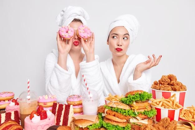 Duas mulheres posam perto de uma mesa cheia de deliciosos petiscos apetitosos, preferem uma refeição enganadora em vez de uma saudável.