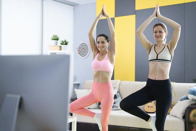 Duas mulheres praticam esportes em casa e ficam em posição de lótus. ioga em casa para iniciantes