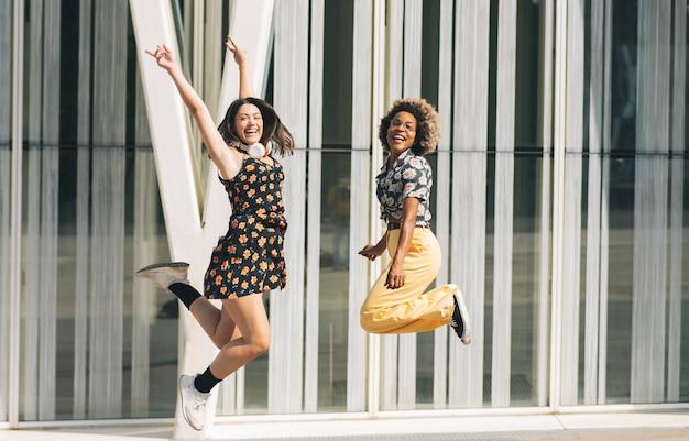 Duas mulheres pulando na rua, multiétnicas