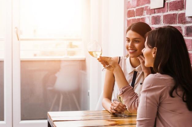 Duas mulheres que apreciam a bebida junto na casa.