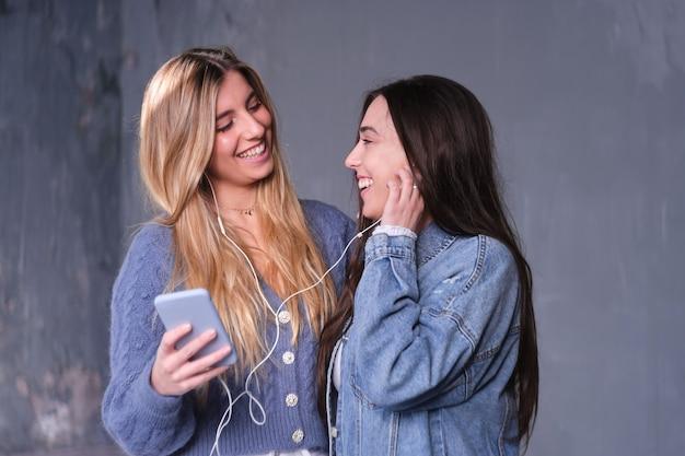 Duas mulheres que compartilham fones de ouvido ouvem música. eles olham um para o outro. sorriso. loira e morena. luz natural do lado de fora. copie o espaço