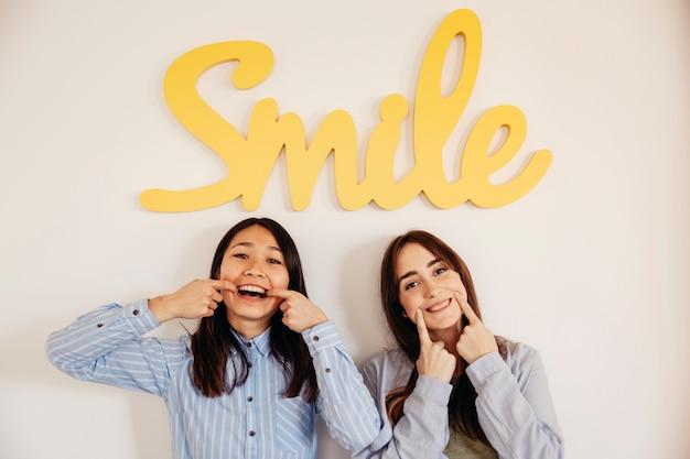 Duas mulheres que mostram sorrisos