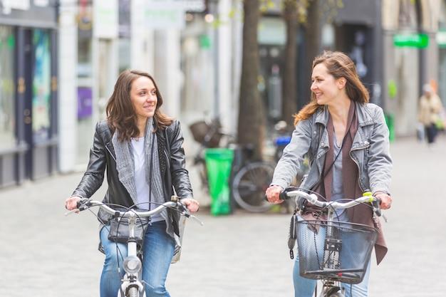 Duas mulheres que vão pela bicicleta em copenhaga.