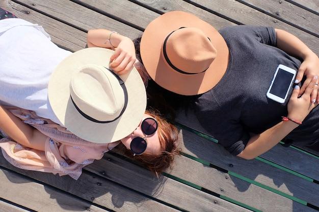 Duas mulheres relaxadas e chapéu. deite-se em uma ponte de madeira que se estende até o mar.