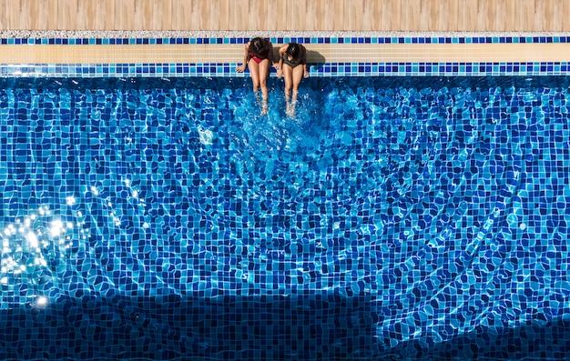 Duas mulheres relaxando e sentado na piscina.