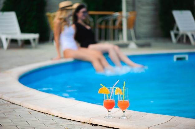 Duas mulheres relaxantes perto da água de férias.