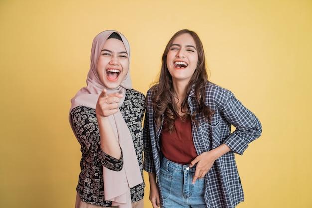 Duas mulheres rindo com vontade com gesto de apontar