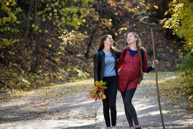 Duas mulheres rindo passear no parque. floresta de outono à distância