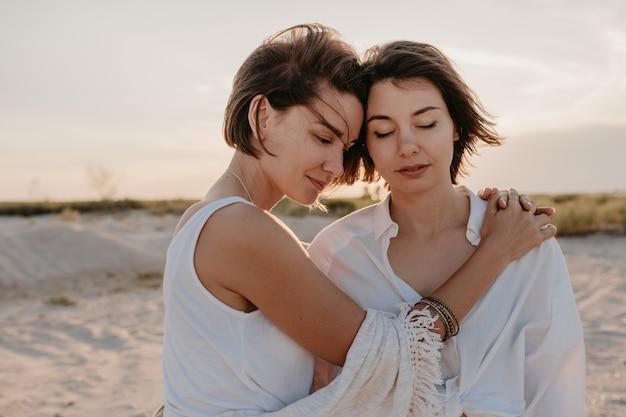 Duas mulheres se divertindo na praia do pôr do sol, romance de amor lésbico gay