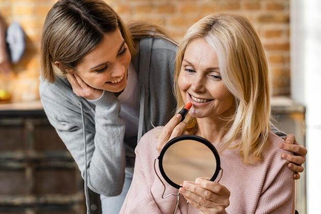 Duas mulheres se maquiando em casa