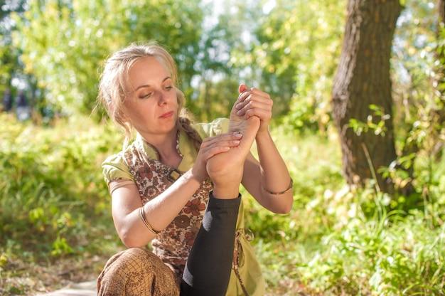 Duas mulheres se massageiam na grama da floresta.