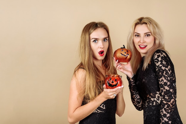 Duas mulheres segurando abóboras de halloween em um fundo bege