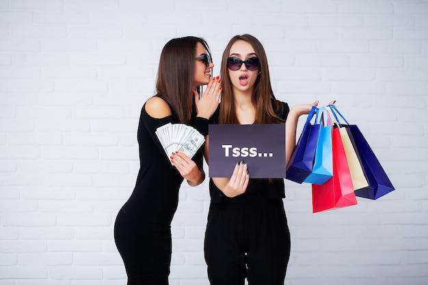 Duas mulheres segurando sacolas pretas sobre fundo claro no feriado de sexta-feira negra
