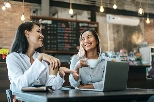 Duas mulheres sentadas e trabalhando com um laptop em uma cafeteria