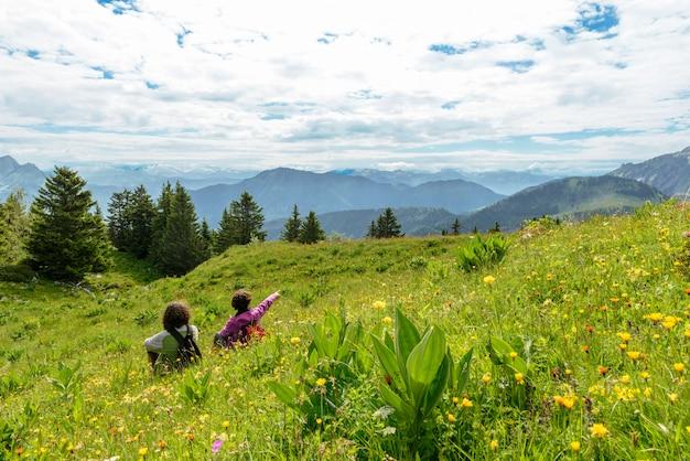 Duas mulheres sentadas na grama e olhando a paisagem