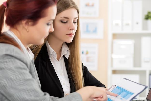 Duas mulheres sentadas no escritório, olhando gráficos e tabelas, discutindo algumas questões