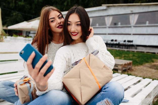 Duas mulheres sentam em um banco do lado de fora e arremessam presentes para smartphone