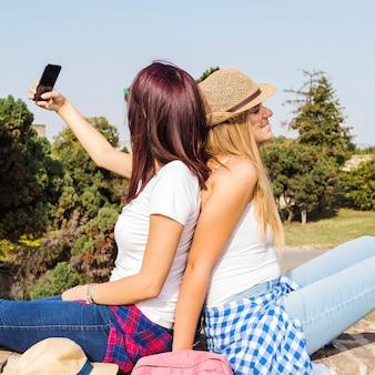 Duas mulheres, sentando, costas, levando, selfie, ligado, telefone móvel