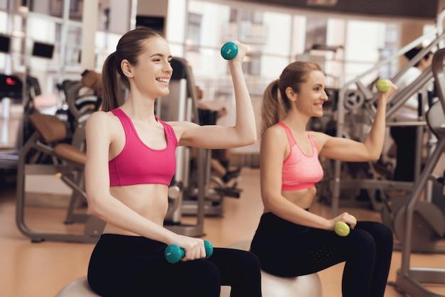 Duas mulheres, sentando, fazendo, exercícios, com, dumbbells, em, a, ginásio