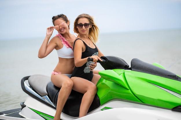 Duas mulheres sexy de biquíni em scooter de água no estilo mar verão