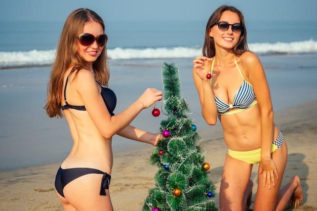 Duas mulheres sexy enfeitam uma árvore de natal na praia